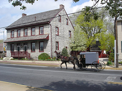 A horse-drawn carriage passes in front of a stone farmhouse with red trim.