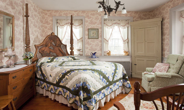 A queen bed with a hand carved wooden headboard featuring two cherubs